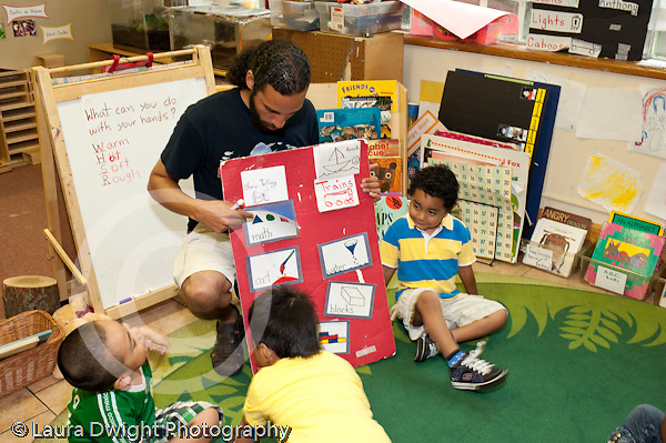 Education Preschool 3-5 year olds circle time  male teacher looking at activity chart with children horizontal