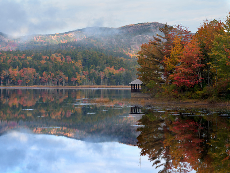 Fog clears from Penobscot Mountain and Little Long Pond during an autumn sunrise on a Maine Land and Garden Preserve near Acadia National Park, Maine, USA