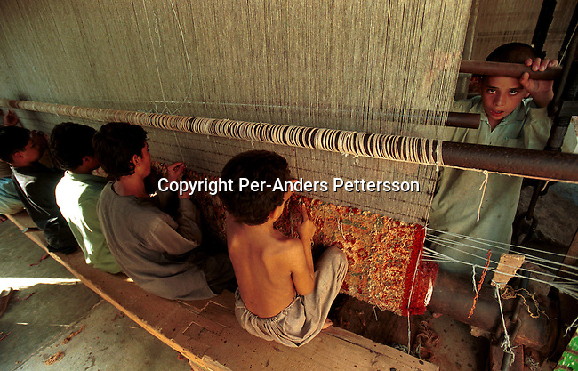 Unidentified young boys weaving an Afghan carpet in an illegal factory on October 1, 2001 in Attock, Pakistan. This village has about 20 carpet factories, where children aged from 5 years old work usually from 4 am to 11 pm in bad conditions and for low wages. This is one of the few chances for Afghan refugees in the village to make money. The children are often beaten and denied school studies. .(Photo: Per-Anders Pettersson/ Grazia Neri.