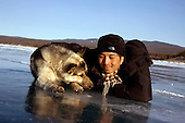 Justin and a dog on the ice near Olkhon Island on Lake Baikal in Siberia, Russia. .They are a group of five people: Justin Jin (Chinese-British), Heleen van Geest (Dutch), Nastya and Misha Martynov (Russian) and their Russian guide Arkady. .They pulled their sledges 80 km across the world's deepest lake, taking a break on Olkhon, the world's forth-largest lake-bound island. They slept two nights on the ice in -15c. .Baikal, the world's largest lake by volume, contains one-fifth of the earth's fresh water and plunges to a depth of 1,637 metres..The lake is frozen from November to April, allowing people to cross by cars and lorries.