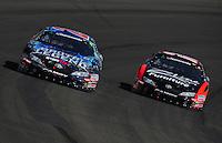 Oct. 10, 2009; Fontana, CA, USA; NASCAR Nationwide Series driver Kyle Busch (20) races alongside Joey Logano during the Copart 300 at Auto Club Speedway. Mandatory Credit: Mark J. Rebilas-