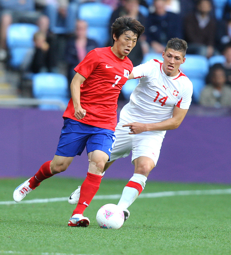 Korea Republic's KIM Bokyung battles with Switzerland's Steven ZUBER ..2012 London Olympics - Football - Group B -Korea Republic v Switzerland - Sunday 29th July 2012 - City of Coventry Stadium - Coventry ..
