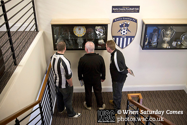 Notts County 150th Anniversary, 18/11/2012. Meadow Lane. Three supporters looking at a trophy cabinet at Meadow Lane, home of Notts County FC on the day of a special Legends Day event marking the club's 150th anniversary. The day-long event featured autograph signing by past and present players, a game between two teams of former players and a screening of a film entitled 'Notts County - the Movie' on a giant inflatable screen. The club were founder members of the Football League in England and call themselves 'the world's oldest Football League club'. Photo by Colin McPherson.