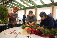 Dorothy Page of Abington, Connie Sandlin of North Philadelphia, and Bobby Morris of Germantown decorate wreaths at the Winter in the Wissahickon event hosted by the Friends of the Wissahickon on December 1. (Dave Tavani/for NewsWorks)