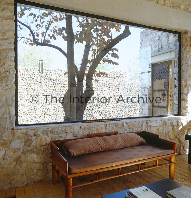 In the sitting area a picture window looks out onto an ancient persimmon tree and a six-metre high wall of stacked local river rock
