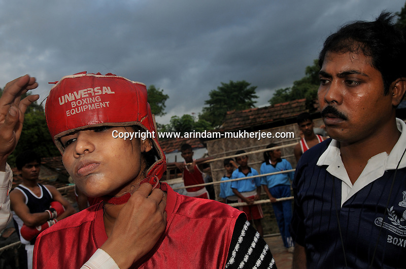 INDIA (West Bengal - Calcutta) August 2010,Shanno Babe prepairing herself before a bout during a practice in a local boxing club. Shakila and Shanno are twins from a poor muslim family of Iqbalpur, Kolkata. . Inspite of their late father's unwillingness to send his daughters to take up  boxing her mother Banno Begum inspired them to take up boxing at the age of 3. Their father was more concerned about the social stigma they have in their community regarding women coming into sports or doing anything which may show disrespect to the religious emotions of his community. Shakila now has been recognised as one of the best young woman boxers of the country after she won the  international championship at Turkey in the junior category. Shanno is also been called for the National camp this year. Presently Shakila and shanno has become the role model in the Iqbalpur area  and parents from muslim community of Iqbalpur have started showing interst in boxing. Iqbalpur is a poor muslim dominated area mostly covered with shanty town with all odds which comes along with poverty and lack of education. - Arindam Mukherjee