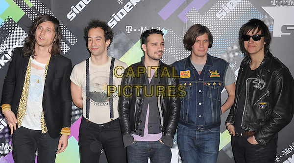 THE STROKES - FAB MORETTI (Fabrizio Moretti), JULIAN CASABLANCAS .at The T-Mobile Sidekick 4G Launch Party held at a private lot in Beverly Hills, California, USA, April 20th 2011..half length band group braces  denim  black leather jacket side sunglasses                                                          .CAP/RKE/DVS.©DVS/RockinExposures/Capital Pictures.