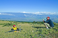 A young newlywed couple on their honeymoon takes a break from their bike ride on Haleakala at a 6,000-ft elevation. In the background are the West Maui Mountains and the central valley of Maui.