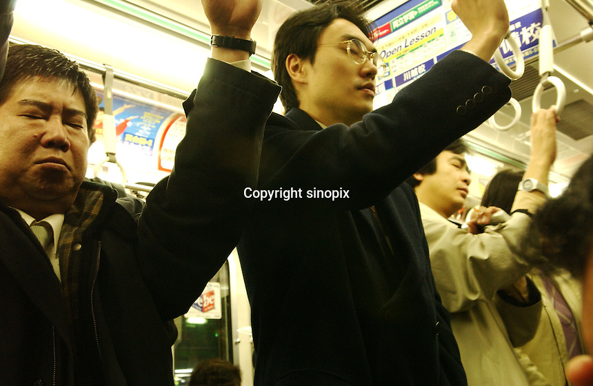 03/2002:  TRANSPORT: TRAIN: :BUSINESSMEN: TOKYO, JAPAN<br /> Businessmen stand in trains during the frantic and busy rush hour period in Tokyo.<br /> Photo by Saigo-Jones/sinopix<br /> ©sinopix