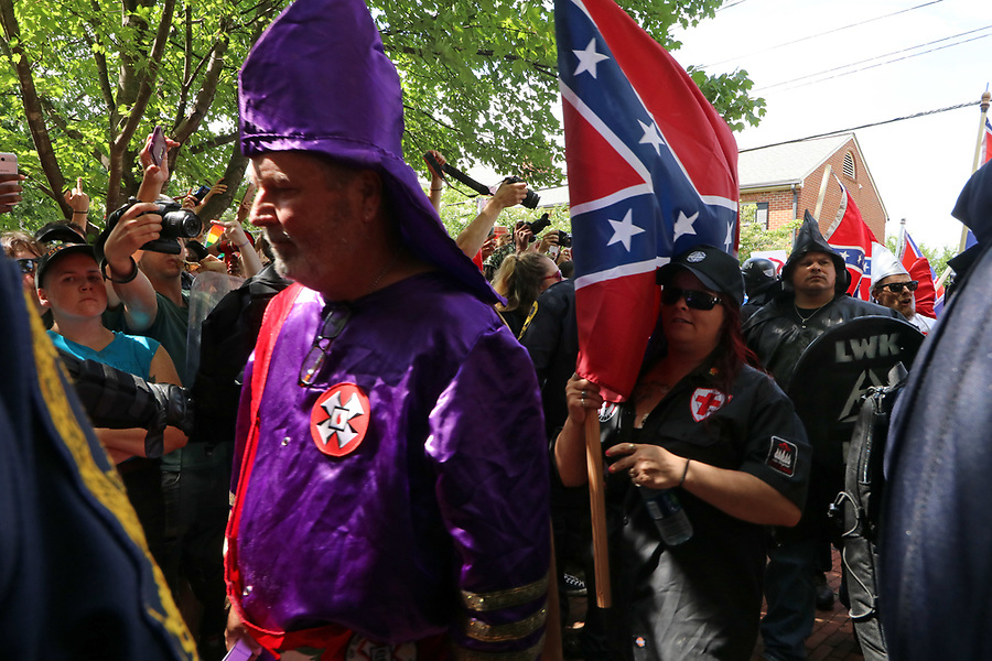 Ku Klux Klan members are shielded by State police as the cross into Jackson Park where they held a rally Saturday in Charlottesville, Va. Several hundred people came out to watch and protest the rally. Photo/Andrew Shurtleff