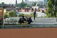 """Fluechtlingsprotest auf dem Dach der Gerhard-Hauptmann-Schule in der Ohlauer Strasse in Berlin-Kreuzberg.<br /> Seit dem 24. Juni 2014 haben harren Fluechtlinge und deren Unterstuetzer auf dem Dach der Gerhard-Hauptmann-Schule aus. Sie hatten sich geweigert dem sog. """"Freiwilligen Umzug"""" zu folgen, der vom Gruenen Bezirksstadtrat Hans Panhoff angeordnet worden war. Die Polizei war bei der als """"Umzug"""" geschoenten Raeumung mit gezogenen Maschinenpistolen angerueckt.<br /> Baustadtrat Panhoff hat am 1. Juli 2014 die polizeiliche Raeumung des Schulgebaeudes beantragt. Einige der Fluechtlinge haben angekuendigt, im Fall der Raeumung vom Dach zu springen. """"Wir haben nichts mehr zu verlieren!"""" sagen sie.<br /> Die Polizei hat seit dem 24. Juni mit ueber 1.000 Beamten saemtliche Strassen um die Schule abgeriegelt. Anwohner duerfen nur nach Personalienfeststellung in ihre Wohnungen, Geschaefte und Gewerbe koennen keine Kundschaft mehr empfangen. Anwohner die gegen das Vorgehen der Polizei protestieren werden von Beamten drangsaliert, geschlagen und verletzt. Mehrere Personen, darunter auch Kinder mussten zum Teil mit Kieferbruch ins Krankenhaus.<br /> Am Abend des 2. Juli 2014 konnte eine Einigung zwischen Fluechtlingen und Bezirksamt eine Einigung erziehlt werden, die den Fluechtlingen einen Verbleib im Hause garantiert. Daraufhin wurden die Polizeimassnahmen beendet.<br /> Im Bild: Polizei beobachtet das Dach der besetzten Schule.<br /> 2.7.2014, Berlin<br /> Copyright: Christian-Ditsch.de<br /> [Inhaltsveraendernde Manipulation des Fotos nur nach ausdruecklicher Genehmigung des Fotografen. Vereinbarungen ueber Abtretung von Persoenlichkeitsrechten/Model Release der abgebildeten Person/Personen liegen nicht vor. NO MODEL RELEASE! Don't publish without copyright Christian-Ditsch.de, Veroeffentlichung nur mit Fotografennennung, sowie gegen Honorar, MwSt. und Beleg. Konto: I N G - D i B a, IBAN DE58500105175400192269, BIC INGDDEFFXXX, Kontakt: post@christian-ditsch.de<br /> Ur"""