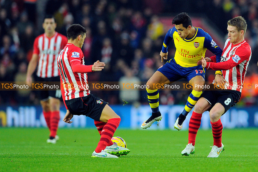 Alexis Sanchez of Arsenal middle vies for the ball with Dusan Tadic of Southampton left and Steven Davis of Southampton right - Southampton vs Arsenal - Barclays Premier League Football at St Mary's Stadium, Southampton, Hampshire - 01/01/15 - MANDATORY CREDIT: Denis Murphy/TGSPHOTO - Self billing applies where appropriate - contact@tgsphoto.co.uk - NO UNPAID USE