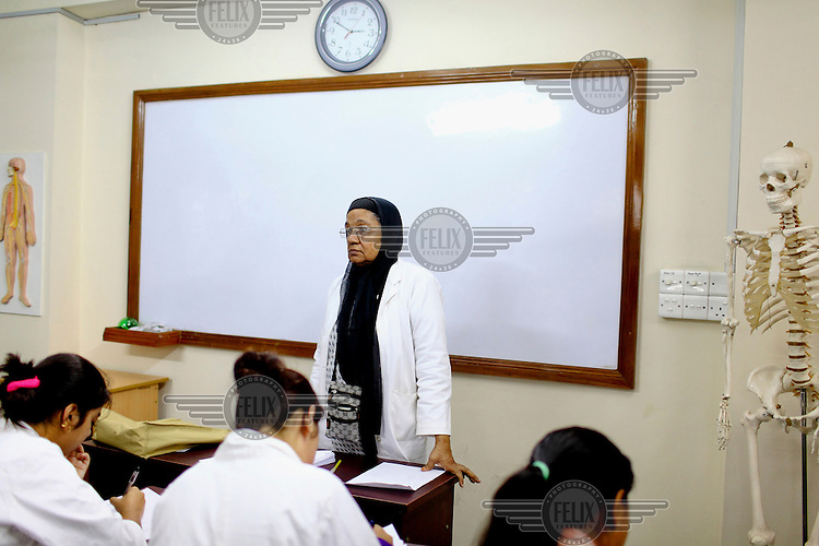 A teacher stands at the front of a class during a science lesson at the Asian University for Women. /Felix Features