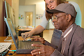 Help with computer skills at a drop in session run by Open Age, a community organisation providing services for the over-50s, at St.Stephen's Church, Bayswater, London.