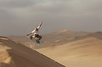 Man sandboarding down a large dune in the Namib Desert near Swakopmund, Namibia