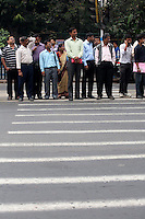 Office workers wait at a pedestrian crossing in central Kolkata.<br /> <br /> To license this image, please contact the National Geographic Creative Collection:<br /> <br /> Image ID: 1925860<br />  <br /> Email: natgeocreative@ngs.org<br /> <br /> Telephone: 202 857 7537 / Toll Free 800 434 2244<br /> <br /> National Geographic Creative<br /> 1145 17th St NW, Washington DC 20036