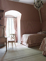 The guest room is in red and white with the wallpaper, curtains and bedding all furnished in the same stripe pattern fabric.