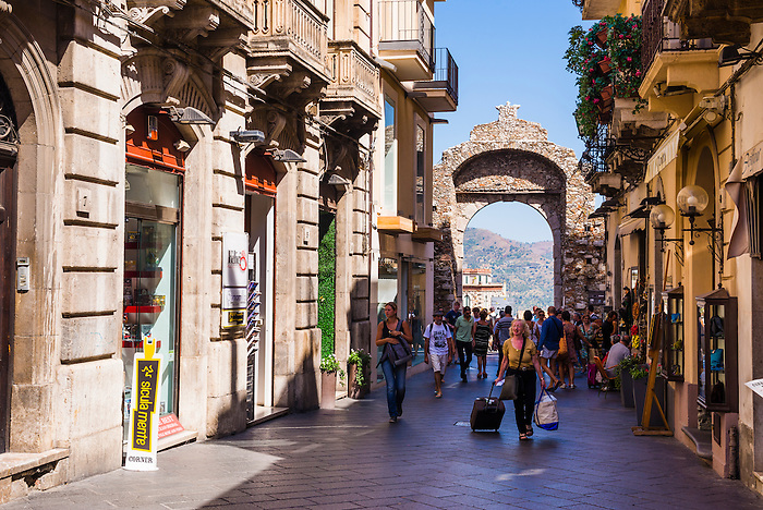 Tourists entering Corso Umberto, the main street in Taormina through the Porta Messina gate, Taormina, Sicily, Italy, Europe. This is a photo of Tourists entering Corso Umberto, the main street in Taormina through the Porta Messina gate, Taormina, Sicily, Italy, Europe.