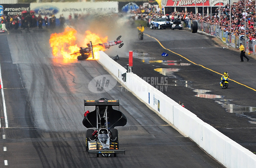 Feb. 21, 2010; Chandler, AZ, USA; NHRA top fuel dragster driver Troy Buff crosses the finish line to win the race asAntron Brown bursts into flames as he crashes during the Arizona Nationals at Firebird International Raceway. A tire from Browns car went over the wall into spectator areas. Mandatory Credit: Mark J. Rebilas-