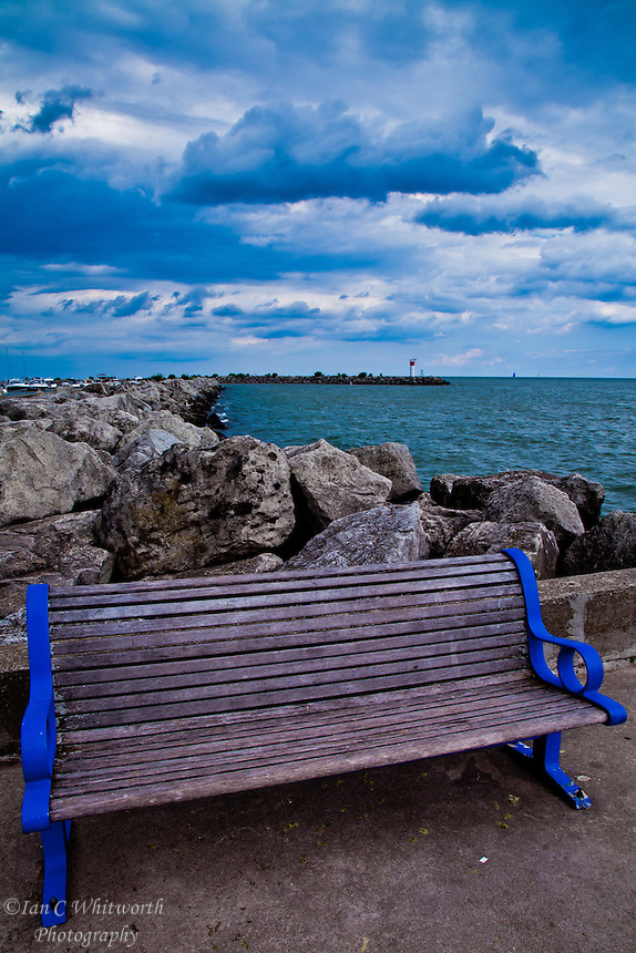 Bronte Harbour bench in Oakville with a interesting sky in the background