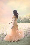 The back of a twirling young faceless woman wearing a fancy peach-colored dress with a beautiful outdoor scenery