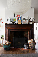 A large wooden fireplace with baskets of wood. The mantelpiece is heavy with picture frames.