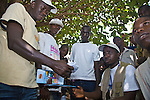 "In many developing countries, transport workers (e.g. long-distance drivers) are a high-risk group for HIV/AIDS because they spend a significant portion of time away from home.  Peer educators trained by Population Services International conduct an interpersonal communication session on HIV/AIDS prevention at ""Kilometre 36,"" a highway junction point 36 km from Guinea's capital city of Conakry."