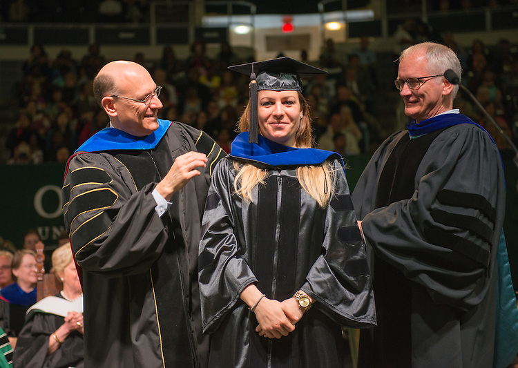 Nora Bunford receives her hood for the doctor of psycholgy from Dean of the College of Arts and Sciences, Robert Frank (Left) and Dr. Steven Evans (Right), Professor and Assistant Chair for Graduate Studies in the Department of Psychology.  Photo by Ben Siegel