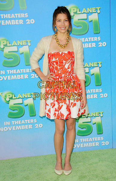 "JESSICA BIEL.arriving at the Columbia Pictures' L.A. Premiere of  ""Planet 51"" at Mann Village Theatre in Westwood, California, USA, .November 14th, 2009..full length strapless red orange and white pattern print dress cardigan long  gold necklace beige ballet pumps flats flat shoes  knitted hand on hip smiling .CAP/RKE/DVS.©DVS/RockinExposures/Capital Pictures"