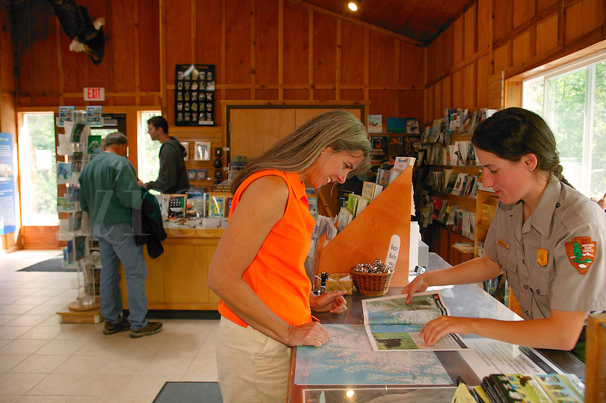 Tourist  being helped Park employee Bonnie Moore at the Exit Glacier Nature Center, Kenai Fjords National Park, Seward, Alaska.