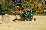 John Deere tractors with roller-bail attachments, rake wheel preparing hay rolls in cut field 1997 model 5400.