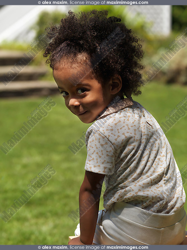 Cute smiling three year old girl looking over her shoulder summertime outdoor portrait