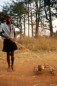 Kapatu, Zambia. Boy playing with a toy made from tins, bamboo and wires.