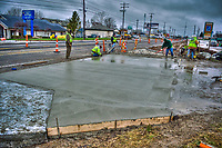 Construction workers struggle to finish the concrete driveway into a shopping center to beat the forecast of heavy rains later in the day. Construction along Westerville Road has been plagued by poor weather as the  first  section of work nears an end.wider lanes and an improved traffic pattern.