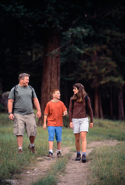 A family of three hiking along the forest's edge in Rocky Mtn Nat'l Park, CO