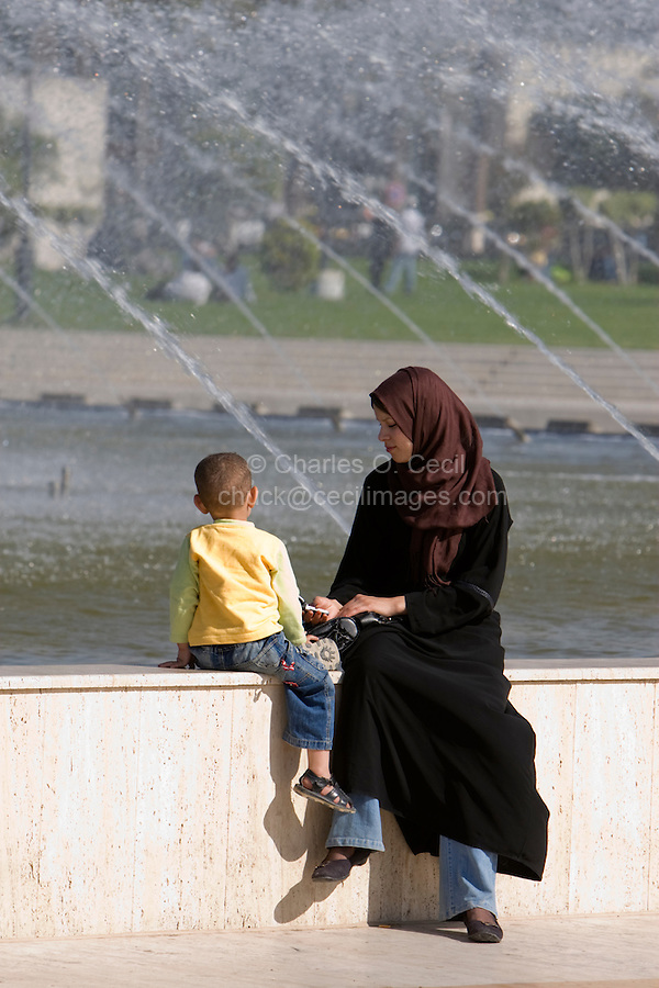 Tripoli, Libya, North Africa - Modern Libyan Women's Clothing Styles as seen in Public Park near the Green Square, downtown Tripoli.  Mother and Son, mother with cell phone.