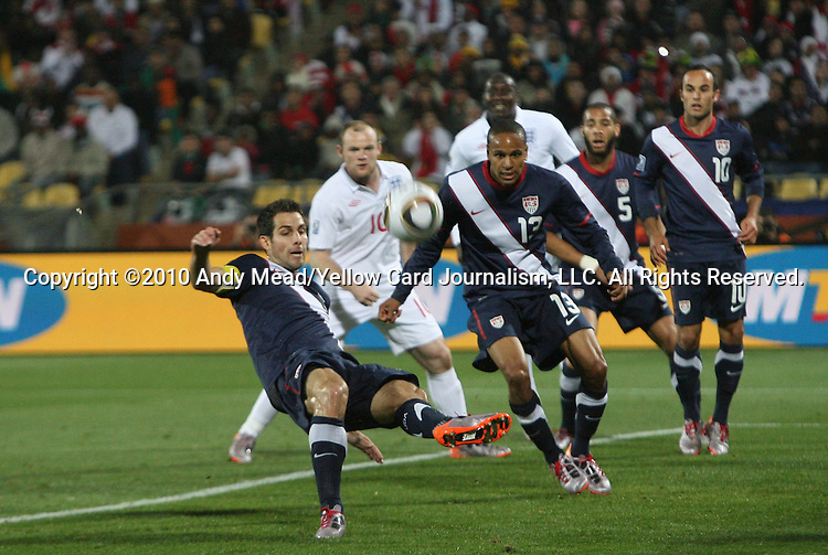 12 JUN 2010: Carlos Bocanegra (USA) (left) clears the ball from the penalty area. The England National Team played the United States National Team to a 1-1 tie at Royal Bafokeng Stadium in Rustenburg, South Africa in a 2010 FIFA World Cup Group C match.