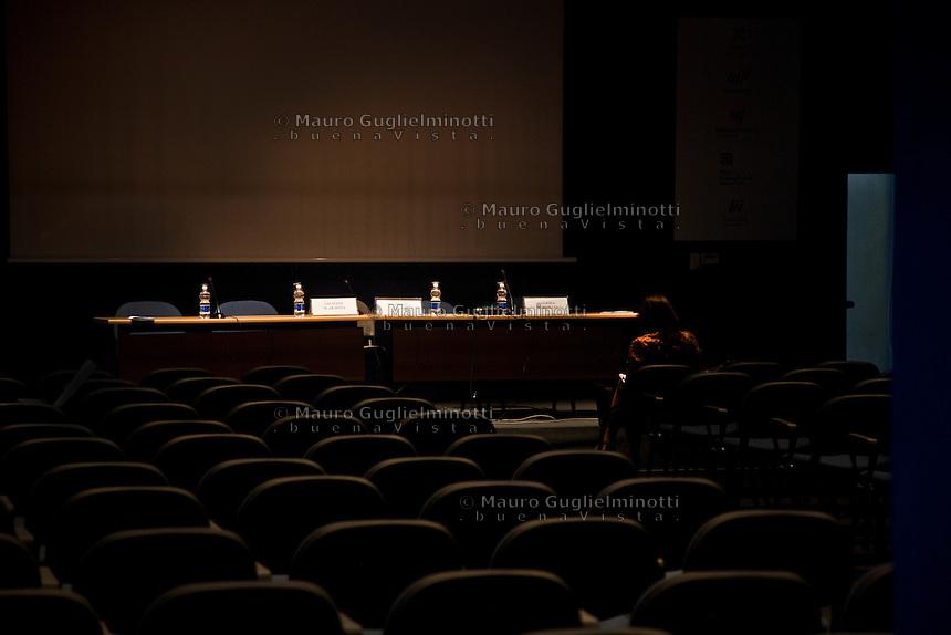 Italia Torino Salone del libro 2014  sala vuota in attesa di un convegno , una signora legge un libro