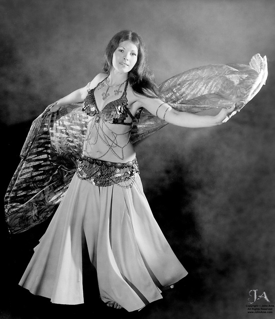Portrait of Carista, pretty brunette belly dancer with flowing veil