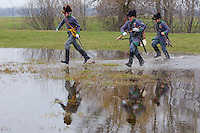 People dressed as Tyrolian hunters cross a pond of water by foot during the re-enactment of the historic battle fought by Hungarians against Austrian soldiers of the Habsburg dynasty in Tapiobicske, 80 km (50 miles) southeast of Budapest, Hungary on April 04, 2013. ATTILA VOLGYI