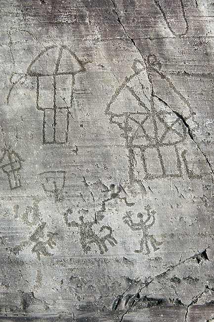 Petroglyph, rock carving, of a village with houses on stilts and a ceremony. Carved by the ancient Camunni people in the iron age between 1000-1200 BC. Rock no 24, Foppi di Nadro, Riserva Naturale Incisioni Rupestri di Ceto, Cimbergo e Paspardo, Capo di Ponti, Valcamonica (Val Camonica), Lombardy plain, Italy