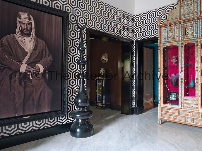 A black and white photograph of King Saud, Prince Faisal's great-grandfather dominates the entrance hall, framed against a Hexagon wallpaper by Cole and Son. The floor is of Carrara marble