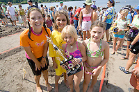 Young girls proudly hold trophy as winners of the sand sculpture contest. Aquatennial Beach Bash Minneapolis Minnesota USA