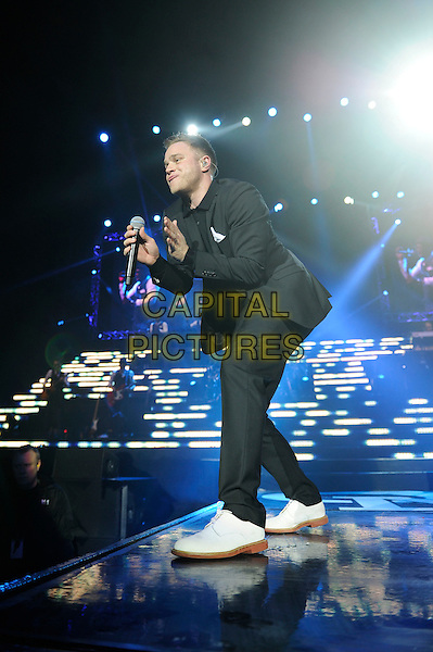 Olly Murs.performing live in concert, o2 arena, Greenwich, London, England. .30th March 2013.on stage gig performance music full length black suit singing white shoes side profile bending .CAP/MAR.© Martin Harris/Capital Pictures.