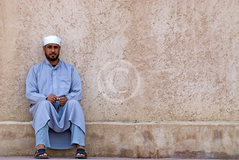 Oman, Buraimi, Arab man, seated against wall