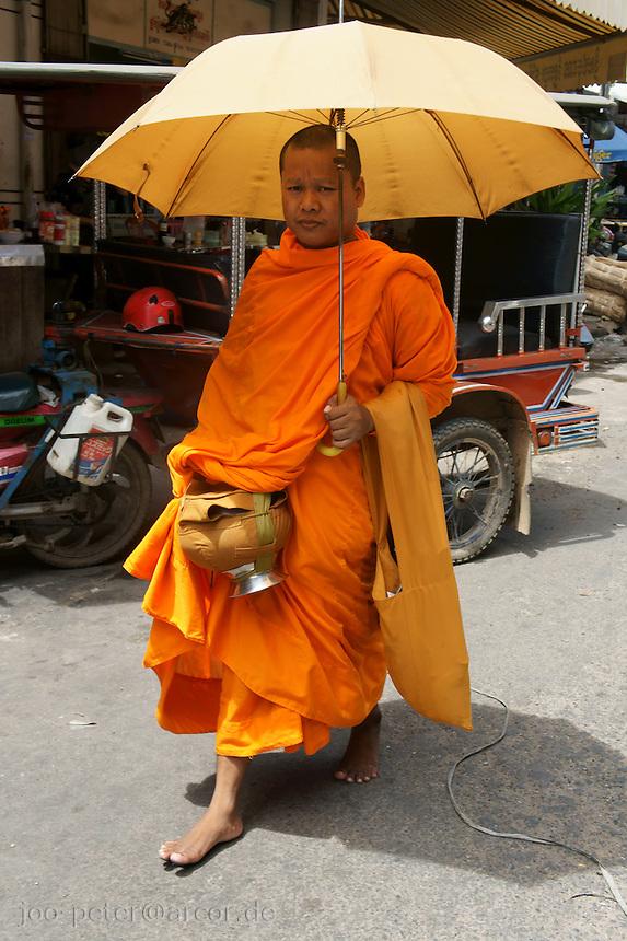monk with umbrella in Phnom Penh, Cambodia, August 2011