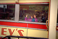 Girl age 5 looking out of famous Mickeys Restaurant window.  St Paul  Minnesota USA