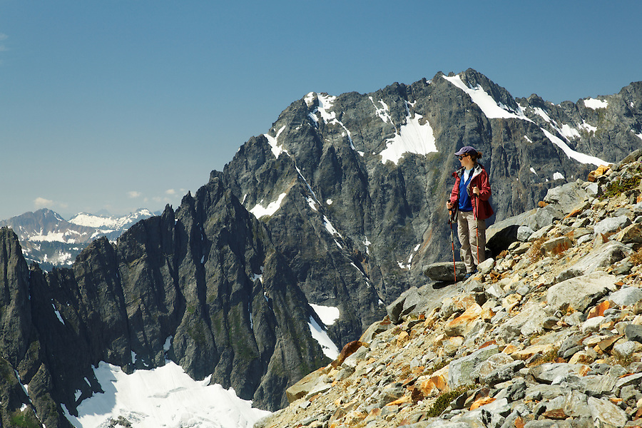 Woman hiking on rocky alpine ridge, Washington's North Cascade Mountains in background, North Cascades National Park, Washington State, USA
