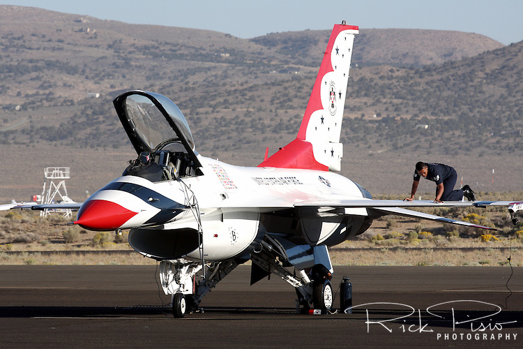A United States Air Force Thunderbirds ground crew member cleans the top surface of the F-16's wing in preparation for the days flight demonstration at the 2008 Reno National Championship Air Races at Stead Field in Nevada. The Thunderbirds were formed in 1956 and have been flying the F-16C Fighting Falcon since 1992.
