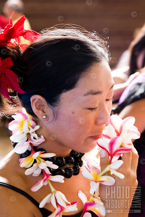 Local Asian woman smelling her plumeria lei after her hula performance
